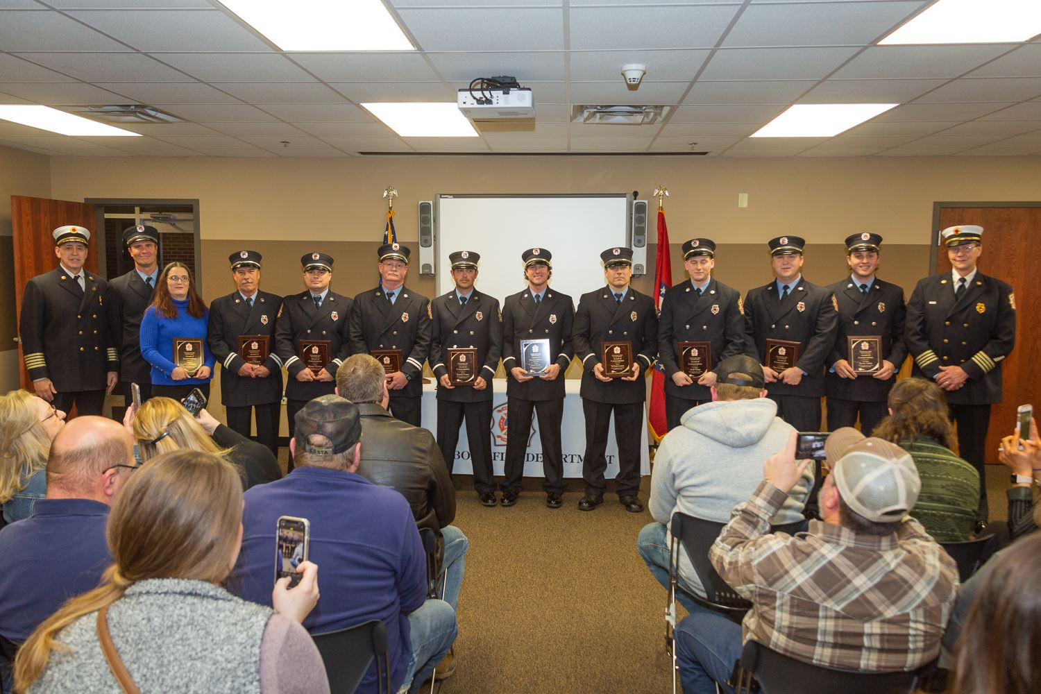 Fire Department Award recipients standing in line in front of audience at awards ceremony holding th