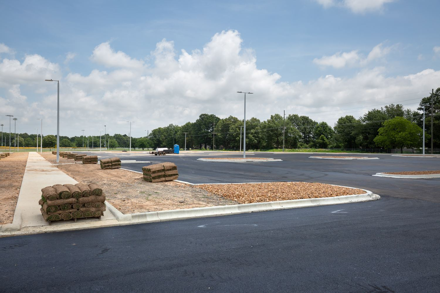 Southside Softball Complex parking lot paved with asphalt and rolls of sod being ready to install.